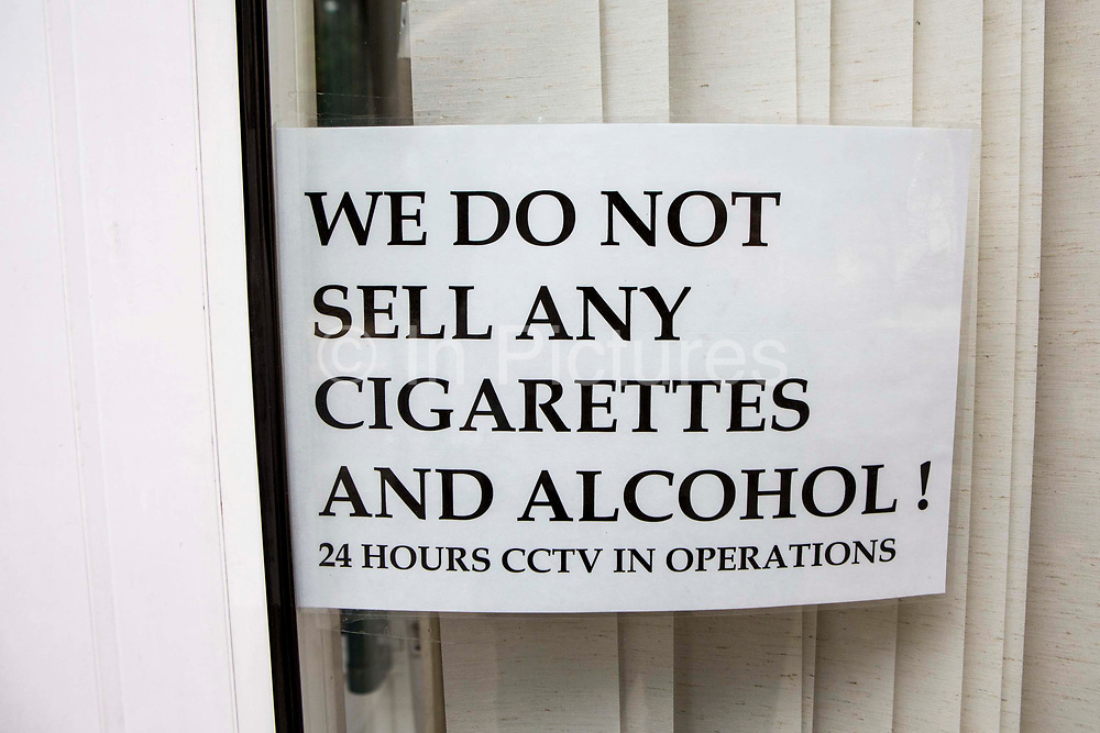 """Window sign stating: We do not sell any cigarettes and alcohol! 24 hours CCTV in operation""""."""