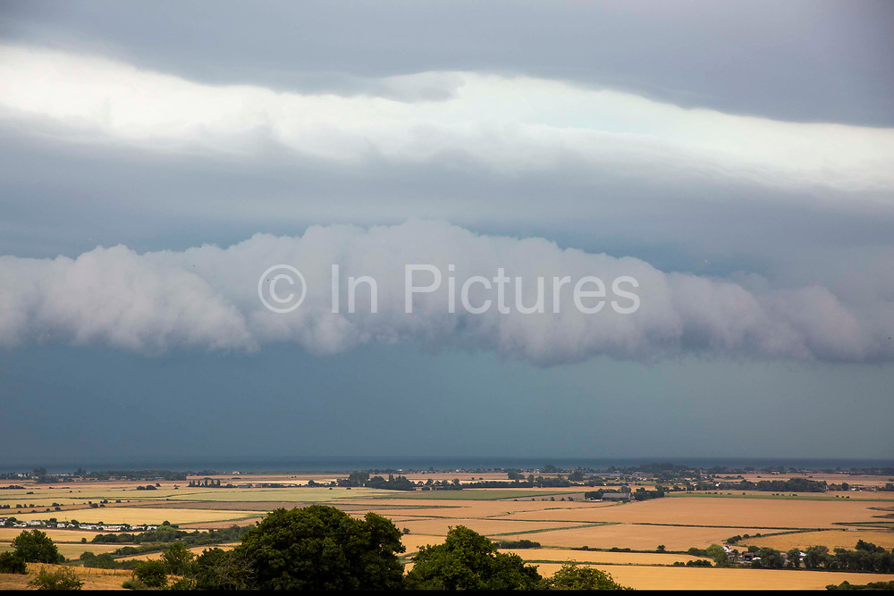 Big grey Arcus rolling storm clouds rolling in off the English Channel across Romney Marsh land near Dungeness, Kent.