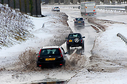 © Licensed to London News Pictures. 4/03/2018. Tredegar, Blaenau Gwent,, South Wales, UK. Vehicles negotiate a large area of flooding caused by melting snow, on a a slip road leading onto the A465 road to Merthyr Tydfil, known as the Heads of the Valleys Road, near Tredegar in Blaenau Gwent, South Wales, UK.  After the horrendous weather condition caused by the Beast from the East meeting Storm Emma in South  Wales, with burst pipes, power failure and people unable to get foos supplies, temperatures have risen and a new threat of melting snow causing flooding has arrived. Photo credit: Graham M. Lawrence/LNP