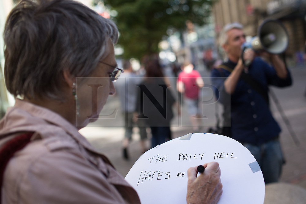 """© Licensed to London News Pictures . 06/10/2013 . Manchester , UK . A woman writes """" The Daily Heil hates me"""" on a placard . A demonstration against the Daily Mail newspaper in central Manchester's St Anne's Square today (6th October 2013) . Photo credit : Joel Goodman/LNP"""