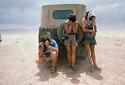 Expedition leader Michael Novacek left, and Paleontologist Mark Norell right and a crew member center take refuge behind a jeep and cover their eyes during a sandstorm in the Gobi Desert near Ukhaa Tolgod.
