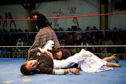 Female wrestler slamming on floor with referee in ring. Lucha Libre wrestling origniated in Mexico, but is popular in other latin Amercian countries, including in La Paz / El Alto, Bolivia. Male and female fighters participate in the theatrical staged fights to an adoring crowd of locals and foreigners alike.