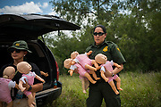 A U.S. Border Patrol agent holds infant manikins in preparation for a demonstration during a 'Border Safety Initiative' media event at the Mexico-U.S. border in Mission, Texas, U.S., July 1, 2019. The infant manikins were handed to media members, who were led on a heavily used migrant path away from the Rio Grande river, in an effort to demonstrate the danger and difficulty of crossing the border with children during the hot summer months.