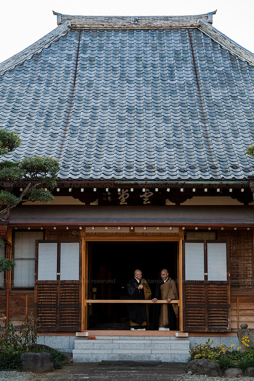 Monks talking at the door of a building in Aoyama cemetery, Tokyo, Japan. Friday November 14th 2014