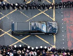 © Licensed to London News Pictures. 03/10/2012. Manchester, UK . The hearse carrying Nical Hughes' coffin with a single rose resting on the roof . 100s of police and public line Deansgate in Manchester City Centre for the funeral of PC Nicola Hughes at Manchester Cathedral . Hughes was murdered in a gun and grenade attack alongside PC Fiona Bone when responding to a suspected burglary at a house in Hattersley in Tameside on 18th September . Dale Cregan is currently on remand , accused of their murder . Photo credit : Joel Goodman/LNP