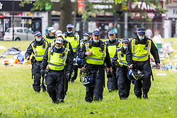 Licensed to London News Pictures. 17/06/2021. London, UK. Police and bailiffs clear an anti-lockdown camp on Shepherd's Bush Green this morning. The demonstrators who have been camping on the green since 31 May 2021 were forced out of their tents this morning with many of their possessions left behind as police in riot gear and on horseback forced everyone out of the west London green space. The protesters have been demonstrating against lockdown, mask wearing, vaccines and testing. Photo credit: Alex Lentati/LNP