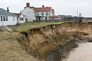 Happisburg, Norfolk, England, 14/03/2006..Abandoned homes where rising sea levels have breached the sea defences, eroding the cliffs and shoreline.
