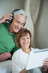 Couple using digital tablet while man with headset, smiling