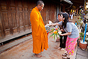 """10 JULY 2011 - AMPHAWA, SAMUT SONGKRAM, THAILAND:   Thai women present a monk with an offering during his morning alms rounds in Amphawa, Thailand, about 90 minutes south of Bangkok. The Thai countryside south of Bangkok is crisscrossed with canals, some large enough to accommodate small commercial boats and small barges, some barely large enough for a small canoe. People who live near the canals use them for everything from domestic water to transportation and fishing. Some, like the canals in Amphawa and nearby Damnoensaduak (also spelled Damnoen Saduak) are also relatively famous for their """"floating markets"""" where vendors set up their canoes and boats as floating shops.      PHOTO BY JACK KURTZ"""