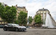 A Ferrari drives by a fountain in Paris, France on May 18, 2012.