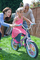 Little girl playing on bike in the garden with her parents,