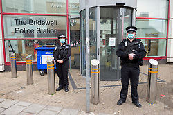 """© Licensed to London News Pictures;22/03/2021; Bristol, UK. Police stand outside Bridewell Police Station the morning after a """"Kill the Bill"""" protest against the Police, Crime, Sentencing and Courts Bill when a police car and a police van were set on fire as police clashed with protesters, and windows of the police station were damaged. The Police, Crime, Sentencing and Courts Bill proposes new restrictions on protests. Photo credit: Simon Chapman/LNP."""