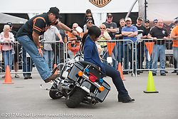 Rob Grimsley, a Harley-Davidson Regional Police Rep, explains how to pick up a bike with very little effort to Terra Green, New Orleans, LA at the Harley-Davidson Display during Daytona Bike Week. Daytona Beach, FL. USA. Monday March 13, 2017. Photography ©2017 Michael Lichter., explains how to pick up a bike with very little effort to Terra Green, New Orleans, LA at the Harley-Davidson Display during Daytona Bike Week. Daytona Beach, FL. USA. Monday March 13, 2017. Photography ©2017 Michael Lichter.