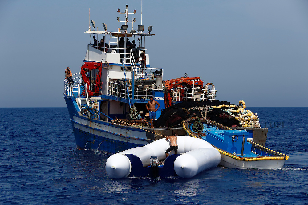 Tunisian fishermen retrieve a rubber dinghy to take its outboard engine after 118 migrants were rescued from it by the Migrant Offshore Aid Station (MOAS) ship MV Phoenix some 20 miles (32 kilometres) off the coast of Libya, August 3, 2015.  118 migrants were rescued from a rubber dinghy off Libya on Monday morning . The Phoenix, manned by personnel from international non-governmental organisations Medecins san Frontiere (MSF) and MOAS, is the first privately funded vessel to operate in the Mediterranean.<br /> REUTERS/Darrin Zammit Lupi <br /> MALTA OUT. NO COMMERCIAL OR EDITORIAL SALES IN MALTA