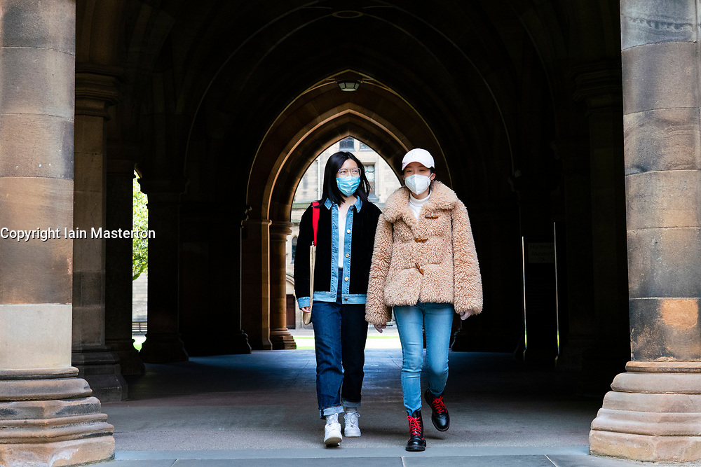 Glasgow, Scotland, UK. 25 September, 2020. Many students at Glasgow University have tested positive for the Covid-19 virus. The Scottish Government has controversially ordered students in several halls of residence where positive cases have spiked, to self-isolate indefinitely. Pictured; Chinese students walking in University cloisters.   Iain Masterton/Alamy Live News