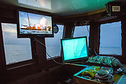 """A trawler boat explodes after picking up a World War Two mine on a television mounted above marine navigation equipment,  installed in the cabin of a fishing boat. Hythe Bay, the English Channel, UK. Luke skippers his boat alone, to keep him company during the trip he has installed a TV. The journey begins with the opening scene of a Bond film where a Trawler boat nets a mine. """"I've caught a few of those in my time"""" say Luke as he navigates around mines, shipwrecks and WWII planes.  Luke is a Folkestone based fisherman out trawling for a 12 hour night shift on a fishing trip in his boat Valentine (FE20), Hythe Bay, the English Channel,(photo by Andrew Aitchison / In pictures via Getty Images)"""
