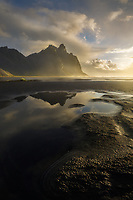Dramatic clouds and reflection of Vesterhorn Mountain at sunrise, South Coast Iceland