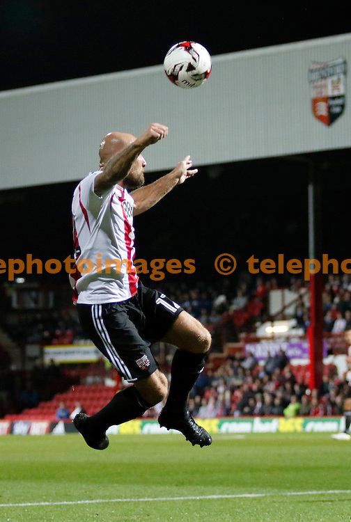 Brentford's Alan McCormack leaps for a header during the Sky Bet Championship match between Brentford and Reading at Griffin Park in London. September 27, 2016.<br /> Carlton Myrie / Telephoto Images<br /> +44 7967 642437