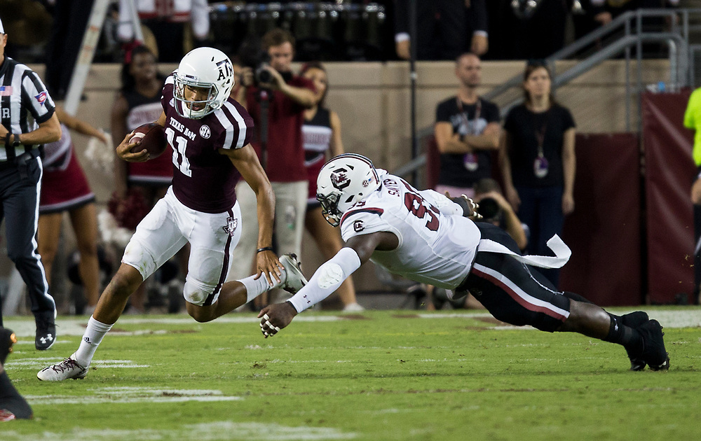 Texas A&M quarterback Kellen Mond (11) evades a tackle by South Carolina defensive lineman Dante Sawyer (95) during the third quarter of an NCAA college football game Saturday, Sept. 30, 2017, in College Station, Texas. (AP Photo/Sam Craft)