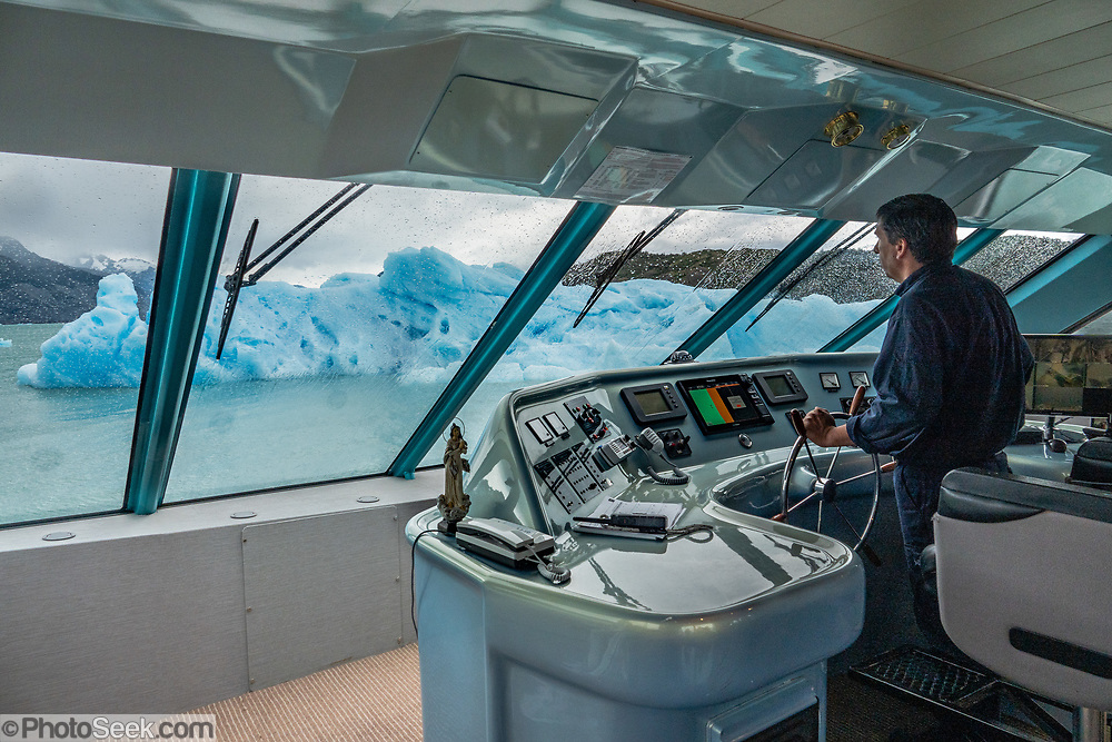 The captain of the Maria Turquesa cruises by a large iceberg seen out the windows on Lake Argentino, in Los Glaciares National Park, Argentina, Patagonia, South America. Starting from La Soledad private port, our ship cruised to the remote and impressive Spegazzini Glacier. The mouth of Upsala Canal allowed viewing distant Upsala Glacier. Landing in Spegazzini Canal Bay allowed a short walk to the old settlers' Las Vacas Station. Finally, navigating the Canal de los Tempanos reached impressive Perito Moreno Glacier where we briefly disembarked certain package-tour members. Remaining passengers cruised back to La Soledad port. Lago Argentino is the biggest freshwater lake in Argentina and reaches as deep as 500 meters (1640 feet). Its outlet, the Santa Cruz River, flows into the Atlantic Ocean. Despite most glaciers worldwide retreating due to global warming, the position of Perito Moreno Glacier's grounded tongue has been a relatively-stable exception for the past 50 years. In contrast, the larger Upsala and Viedma glaciers located north of Perito Moreno have retreated dramatically. Scientists say that nearly 90 percent of the glaciers in Antarctica and Patagonia are melting quickly (2009 data). Located 78 kilometers (48 mi) from El Calafate, Perito Moreno Glacier was named after explorer Francisco Moreno, a pioneer who studied the region in the 1800s and defended the territory of Argentina during the international border dispute with Chile. Los Glaciares National Park is honored on UNESCO's World Heritage List.