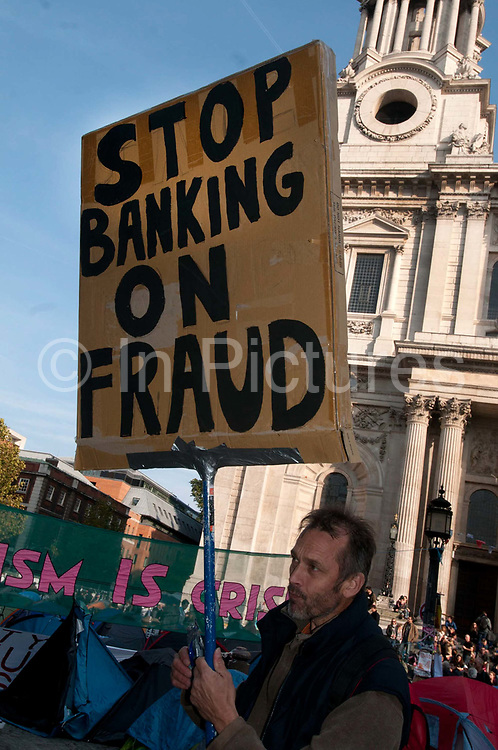 Occupy London October 23rd 2011. St Paul's Cathedral. A man holds a placard saying Stop Banking on Fraud