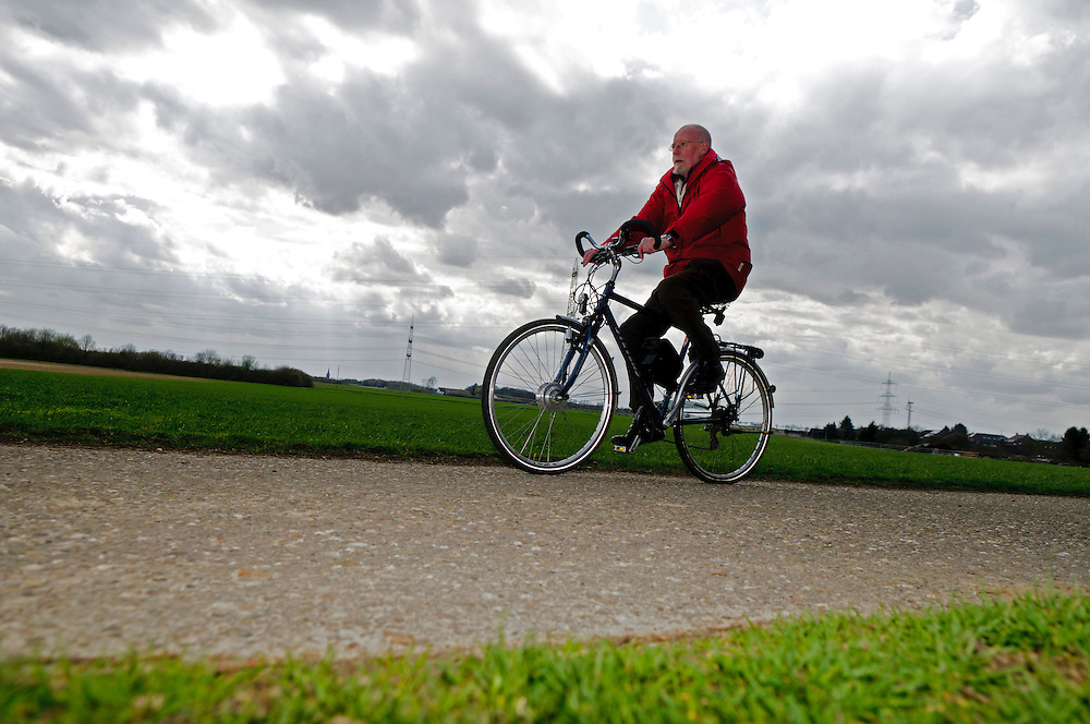 Deutschland, Ein Rentner auf einem Elektrofahrrad auf einem Feldweg vor Acker und Stromleitungen    Germany, A pensioner on an electric bicycle on a dirt road in front of a field and power lines