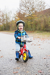 Little boy driving his walking bike on a street while laughing