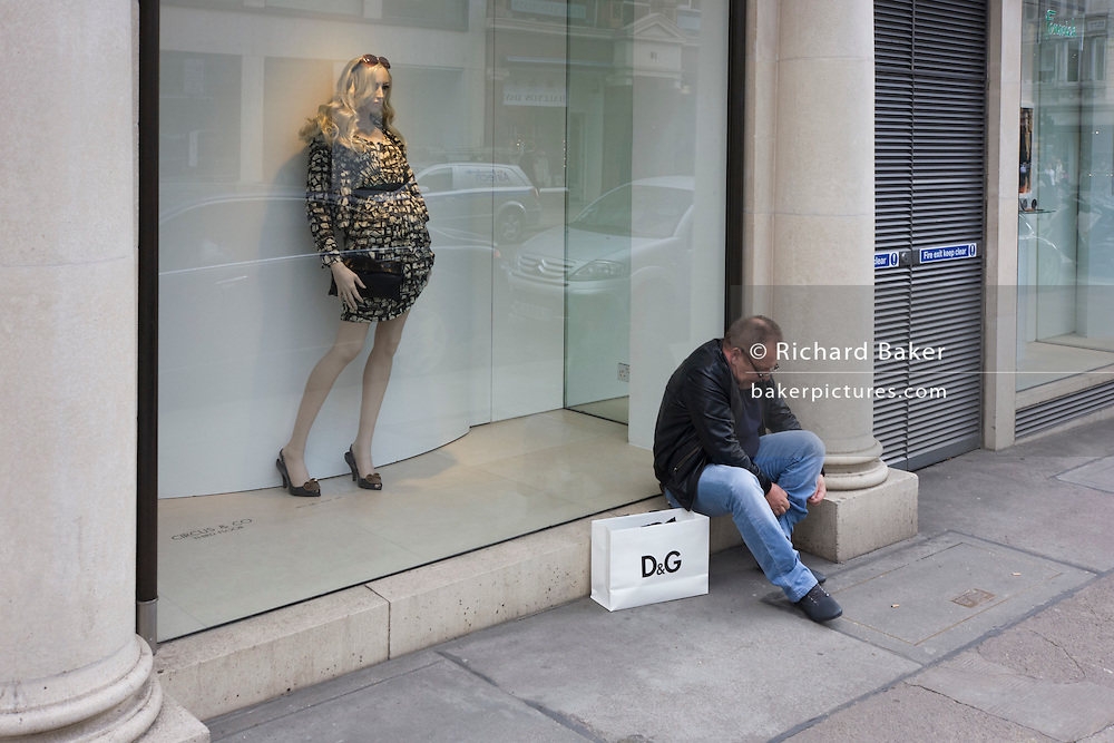 A male shopper adjusts his trouser leg, sitting by a shop window with a mannequin seemingly hitching up her skirt.