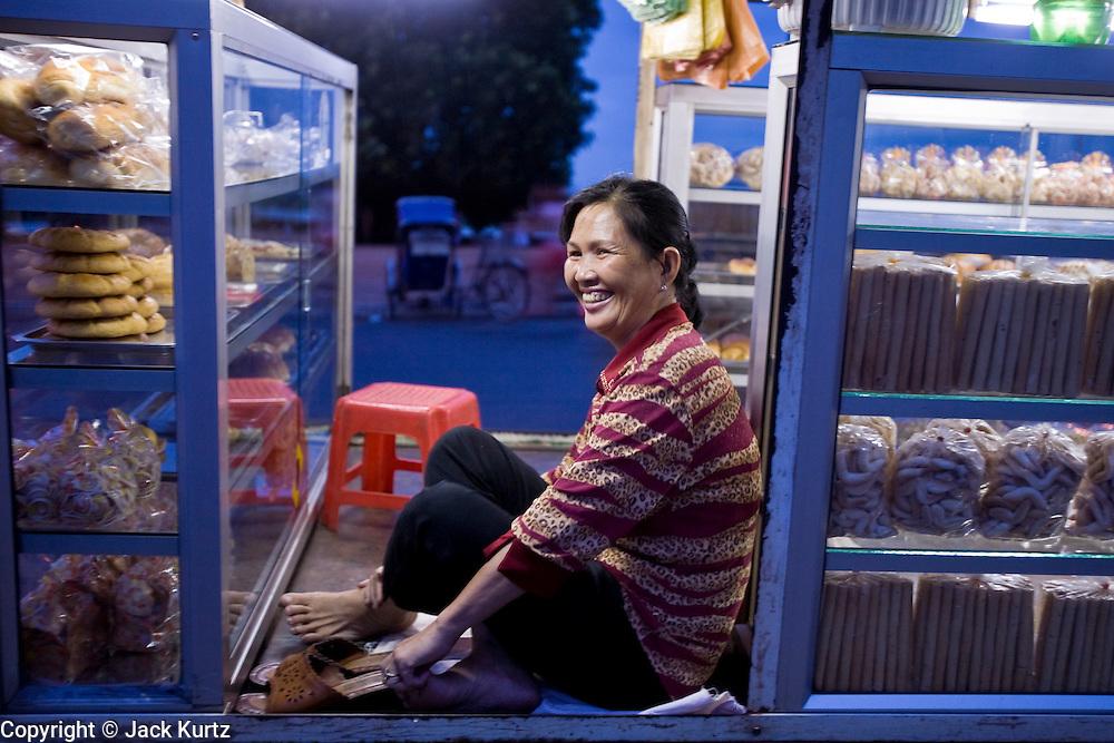29 JUNE 2006 - PHNOM PENH, CAMBODIA: A woman sells baked goods from her van/bakery shop parked on Sisowath Quay, the main riverside boulevard in Phnom Penh, Cambodia. Photo by Jack Kurtz / ZUMA Press