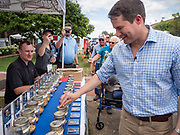 17 AUGUST 2019 - DES MOINES, IOWA: Representative SETH MOULTON (D-MA), right, drops a kernel of corn into a bottle at the corn voting booth at the Iowa State Fair Saturday. Each candidate has a bottle and the vote is tallied at the end of every day. Moulton, a US Marine veteran who served in Iraq, is running to be the Democratic candidate for the US Presidency in 2020 and spent Saturday campaigning at the fair. Iowa traditionally hosts the the first selection event of the presidential election cycle. The Iowa Caucuses will be on Feb. 3, 2020.         PHOTO BY JACK KURTZ