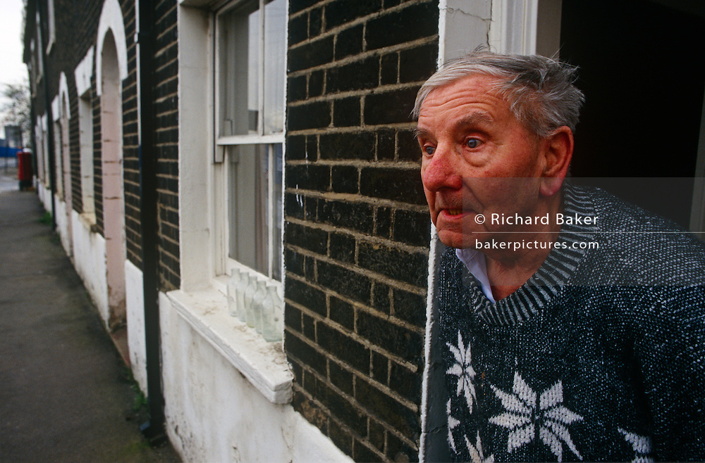 An elderly gentleman looks out from his urban cottage opposite the new Millennium Dome, soon to force him from home.