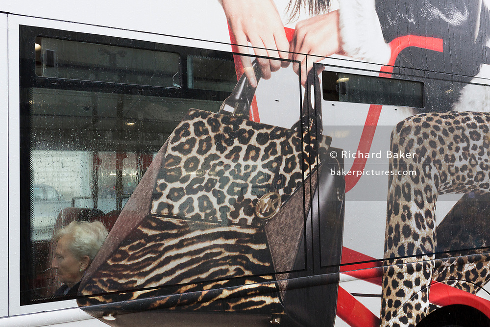 A grey-haired lady passenger sits in the window of a London bus that features an ad of style and fashion while stopped at Victoria Station, on 17th October 2019, in London, England.