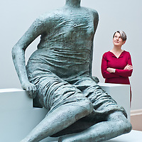"""London, UK - 13 May 2013: Penelope Curtis, director at Tate Britain poses for a picture next to a sculpture by Henry Moore entitled """"Draped Seated Figure 1957-8"""". The new chronological presentation of the world's greatest collection of British art will allow visitors to experience the national collection of British art in a continuous chronological display from the 1500s to the present day."""