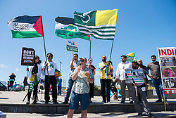 © Licensed to London News Pictures; 12/06/2021; Hayle, Cornwall UK. G7 summit in Cornwall. Supporters of Kashmir and Palestine hold flags at the Resist G7 coalition of protest groups protest in Hayle on the second day of the G7 summit. The protest included supporters of Palestine and of Kashmir as well as anti-war groups and socialists and trade unionists. Photo credit: Simon Chapman/LNP.
