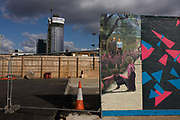2012 Olympic wasteland and PR fantasy on a hoarding near the sports arenas in Stratford, East London. A landscape of utopian harmony and nature is viewed on the construction site board that surrounds a vacant plot a kilometre south of the Olympic Park and stadium site. In the background is a new housing tower block by design and build contractor, Ardmore for Genesis Housing Association, 150 High Street, Stratford, 704 homes, in five new residential blocks, one of which, at over 132 metres, will be one of the highest residential towers in London. This landscape is more dystopian however as the reality of the empty lot is not what is promised by the imagery on the hoarding.