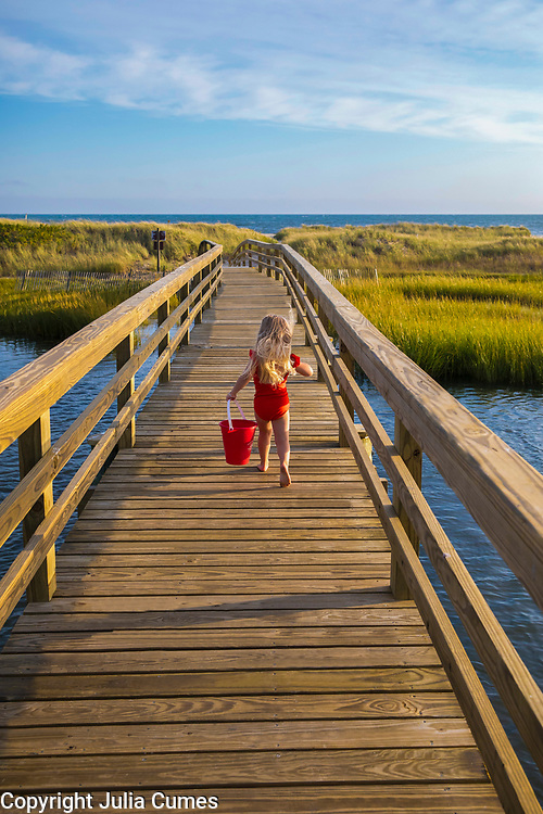 A little girl runs across a bridge  to the beach with her red bucket on a Cape Cod summer day.