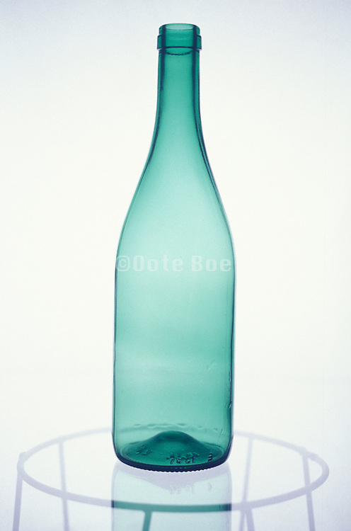 still life of tall green bottle on glass table