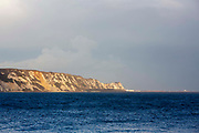 A view across rough seas of the famous chalky White Cliffs of Dover from Folkestone, Kent, England, United Kingdom.