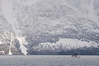 A ski/sail expedition motors the fjords of the Lyngen Alps, Norway.