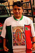 Male pilgrim to the Basilica de Guadelupe next to pick up holding Our Lady of Guadelupe shirt.