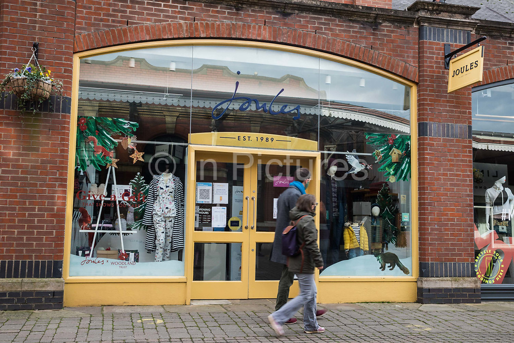 """Two people walk past a branch of fashion chain Joules on the second day of England's second coronavirus lockdown on 6 November 2020 in Windsor, United Kingdom. Only retailers selling """"essential"""" goods and services are permitted to remain open to the public during the second lockdown but Joules has reported a 35% increase in online sales in 2020."""