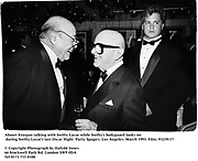 Ahmet Ertegun talking with Swifty Lazar while Swifty's bodyguard looks on at Swifty Lazar's last Oscar Night  Party. Spago's. Los Angeles. March 1993. Film. 93239/17<br />