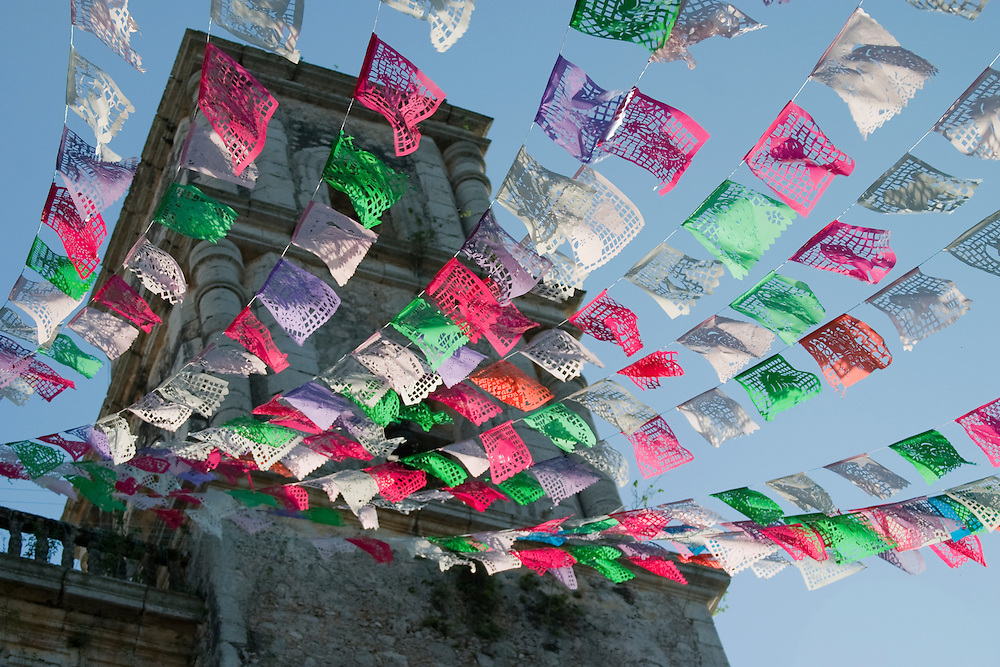 Mexico, Yucatan, Valladolid, La Parraquia de San Servacio church on Plaza Mayor, with colorful flags fluttering in wind