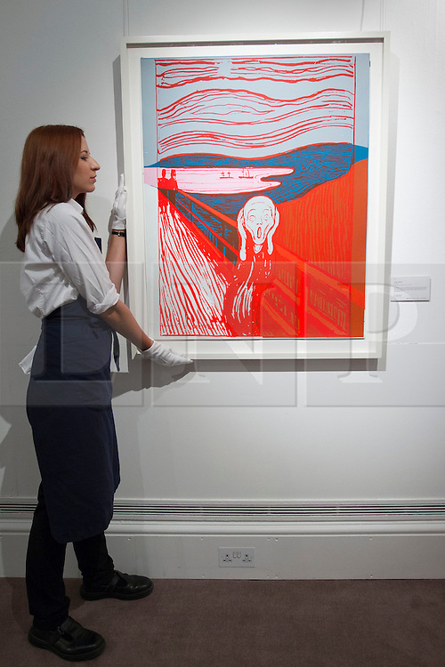 © Licensed to London News Pictures. 13/09/2013. London, UK. Two Sotheby's employee holds a screen print of Andy Warhol's 'Scream (After Munch)' (1984) (est. GB£100,000-150,000) at the press view for Sotheby's 'Prints and Multiples Sale' on New Bond Street in London today (13/09/2013). The auction, set to take place on the 17th of September, includes works by Munch, Rembrandt, Basquiat, Warhol and Picasso. Photo credit: Matt Cetti-Roberts/LNP