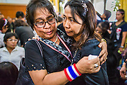 27 JANUARY 2014 - BANGKOK, THAILAND:  Mourners comfort each other at the bathing rites for anti-government leader Suthin Taratin at Wat Sommanat Rajavaravihara in Bangkok. In Thai tradition, after death a bathing ceremony takes place in which relatives and friends pour water over one hand of the deceased. Suthin was a core leader of the People's Democratic Force to Overthrow Thaksinism (Pefot), one of several organizations leading protests against the elected government of Thai Prime Minister Yingluck Shinawatra. He was murdered Sunday, Jan. 28, while he was leading a rally to prevent voters from reaching a polling center in the Bang Na district of Bangkok.    PHOTO BY JACK KURTZ