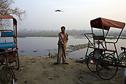 A homeless cycle rickshaw driver dresses at a parking lot next to the Yamuna River where he sleeps. New Delhi, India.