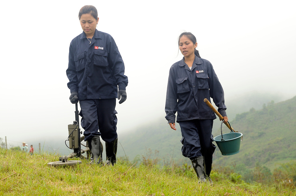 """Mines Advisory Group, Technicians, Sia Thorthongyer, age 19 (left) and Vonekham Dalavong, age 29 (right), use a metal detector and shovel to uncover live bombs hidden in the soil.  Sia and Vonekham said, """"The first time we found a bomb we were afraid.  But we have good training and team work.  We have found many bombs, now it is just normal.  But, if we see a snake - we drop everything and run!"""" ..Laos was part of a """"Secret War"""", waged within its borders primarily by the USA and North Vietnam.  Many left over weapons supplied by China and Russia continue to kill.  However, between 90 and 270 million fist size cluster bombs were dropped on Laos by the USA, with a failure rate up to 30%.  Millions of live cluster bombs still contaminate large areas of Laos causing death and injury..The US Military dropped approximately 2 million tons of bombs on Laos making it, per capita, the most heavily bombed country in the world.   ..The women of Mines Advisory Group (MAG) work everyday under dangerous conditions removing unexploded ordinance (UXO) from fields and villages...***All photographs of MAG's work must include (either on the photo or right next to it) the credit as follows:  Mine clearance by MAG (Reg. charity)***."""