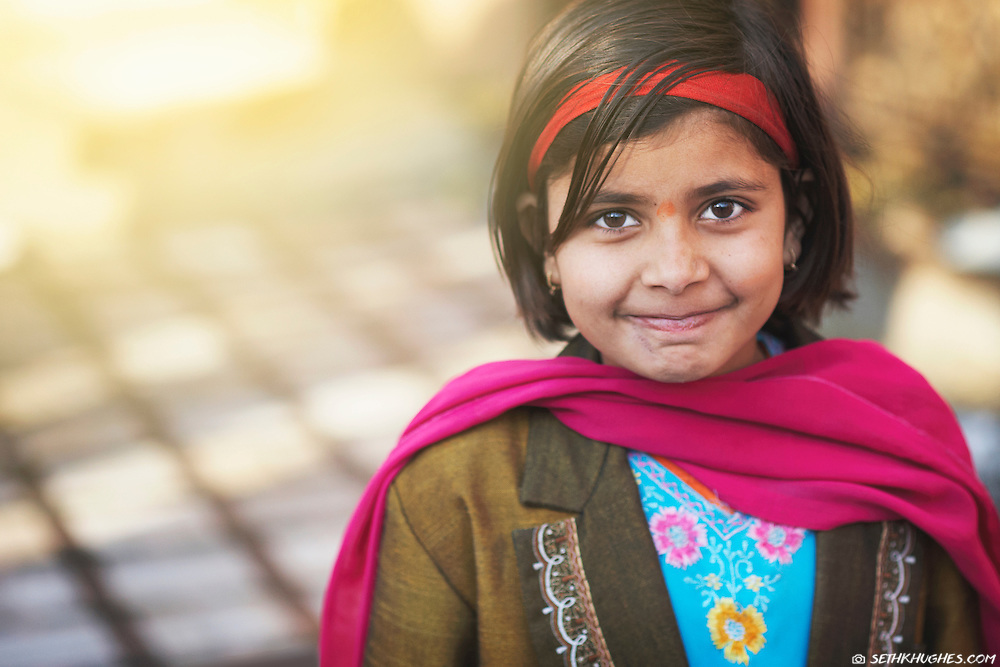 A young Indian girl smiles for a portrait in the rural town of Bikaner, Rajasthan