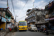 A school bus passes road works along the main street through the centre of Besishahar on the 10th of March 2020, Besishahar, Lamjung District, Gandaki Pradesh, Nepal. Besishahar is a small town, municipality and the district headquarters of Lamjung District in Gandaki Pradesh, Nepal.