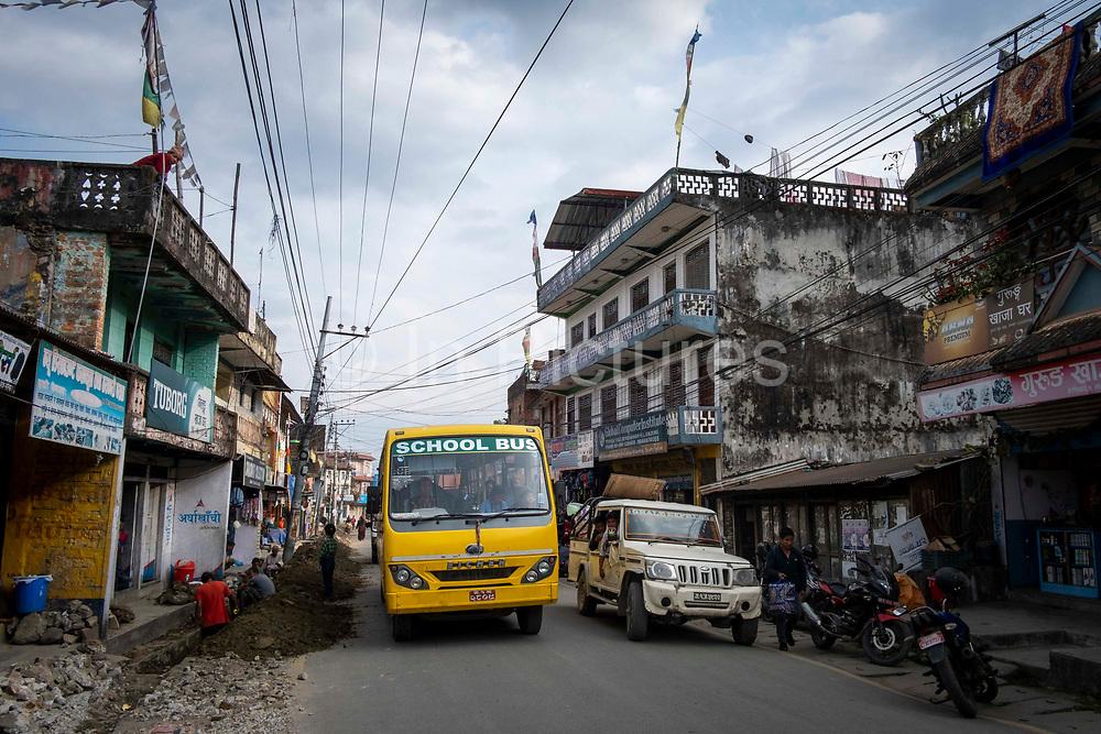 A school bus passes road works along the main street through the centre of Besishahar on the 10th of March 2020, Besishahar, Lamjung District, Gandaki Pradesh, Nepal. Besishahar is a small town, municipality and the district headquarters of Lamjung District in Gandaki Pradesh, Nepal.
